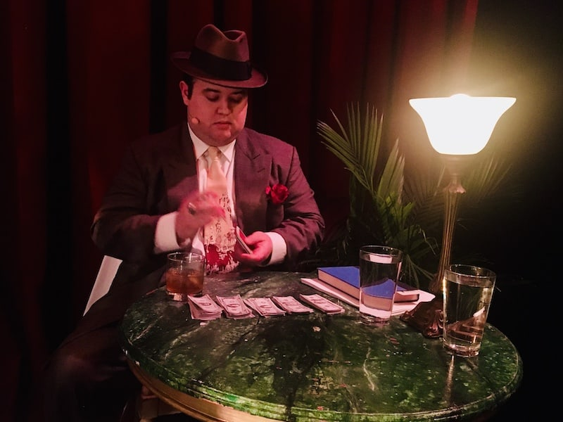 In-game: Rhett King shuffling cards at a small table covered in money.