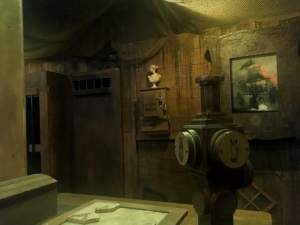 In-game: View of the pirate ship with a partial map in the foreground and art in the background.