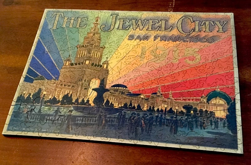 "Image of an intricate wooden jugsaw puzzle depicting art from the San Francisco World's Fair. ""The Jewel City"" shows a tower with lights matching teh colors of the rainbow emerging from it."