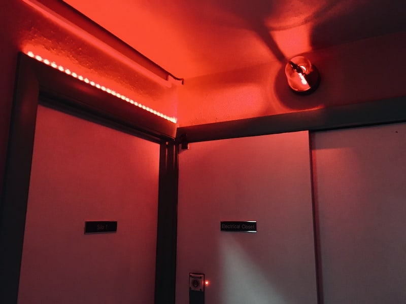 In-game: a small dim room lit by a red alarm light.