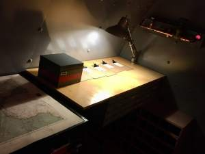In-game: a large wooden workbench with a light.