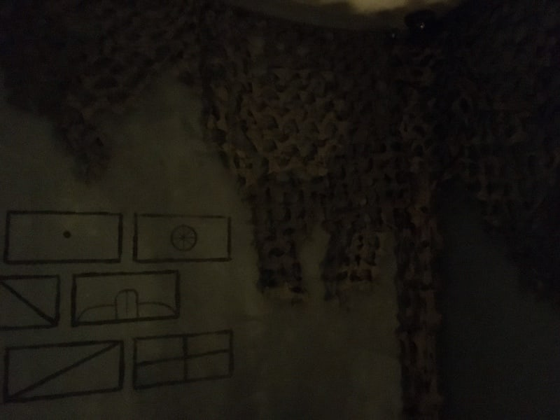 In-game: A concrete wall with strange flags drawn on them surrounded by camouflaging material.