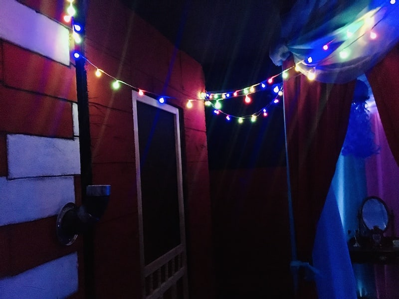In-game: Trailers and tents lit with strings of lights.