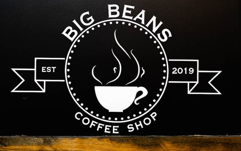 In-game: Closeup of the Big Beans Coffee Shop logo, EST 2019.