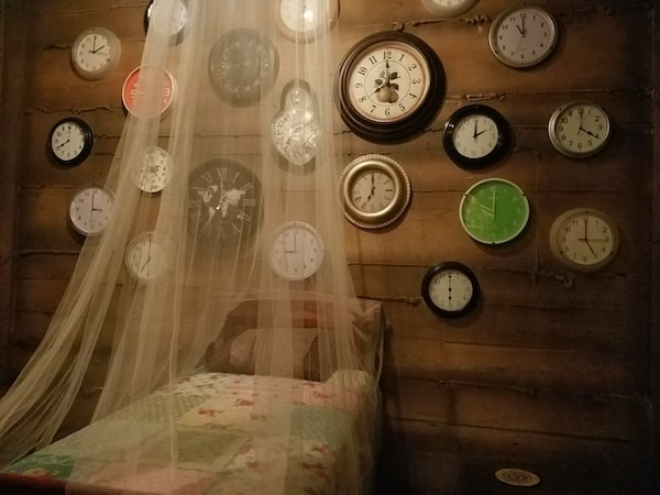A bed draped with sheer fabric sits under a wall covered with various clocks.