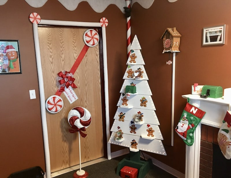 In-game: A white christmas tree shelf covered in gingerbread cookie ornaments beside a fireplace decorated with stockings.