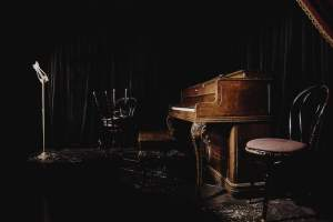 In-game: the piano and microphone on the stage of an old cabaret.