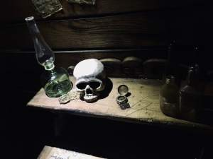 In-game: A desk with a lantern, compass, and skull resting on it.