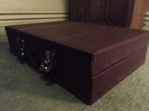 In-game: closeup of an oversized briefcase locked and on the floor.