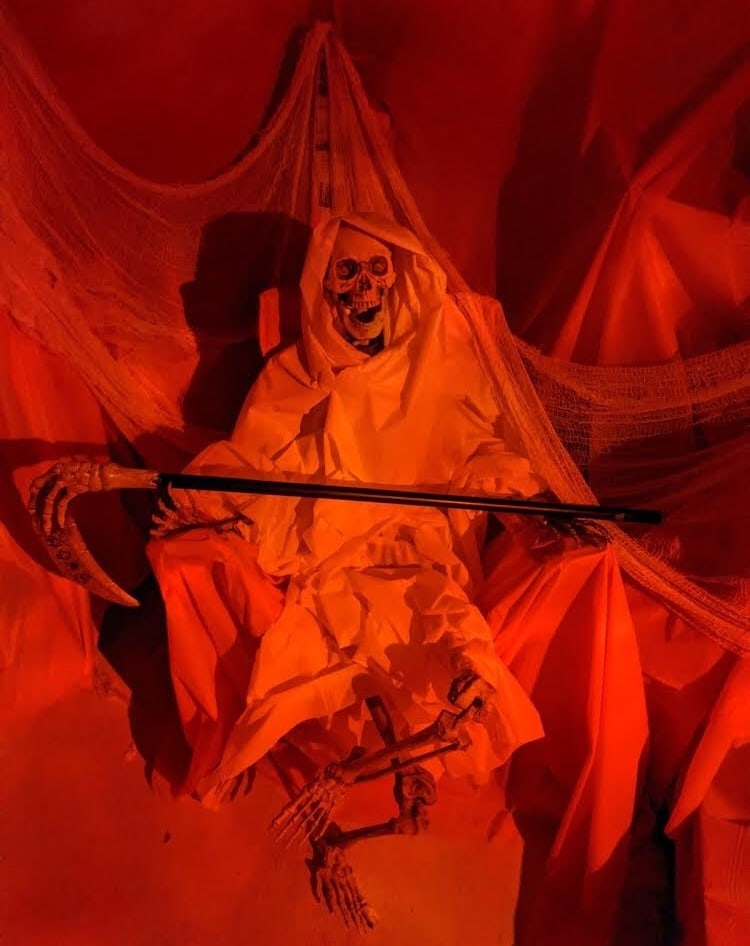 A white cloaked skeleton holding a scythe.