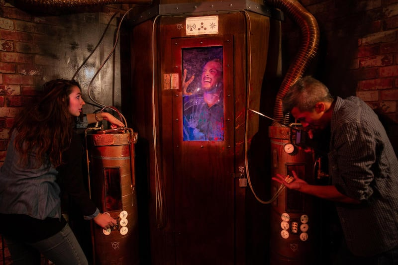 In-game: 2 people operating a chamber occupied by a third person.