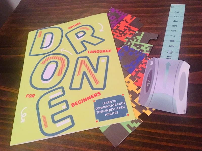 Drone Language for Beginners guide, beside a few paper cut items.
