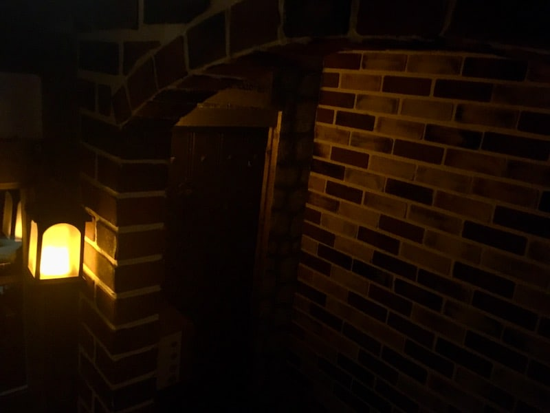 In-game: A brick building at night lit by lantern.
