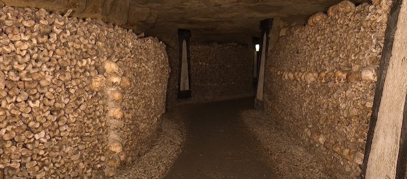 A tunning within the Catacombs of Paris. The walls are linked with human bones.