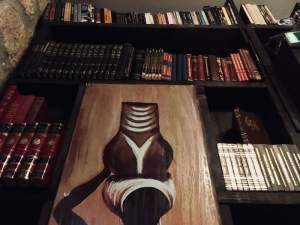 In-game: A tall bookshelf decorated in African art.