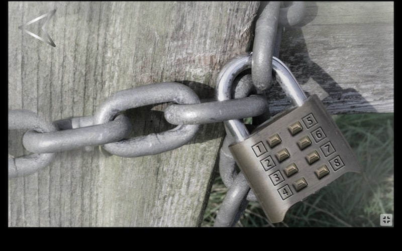 A number padlock binding a heavy chain around a wooden gate.