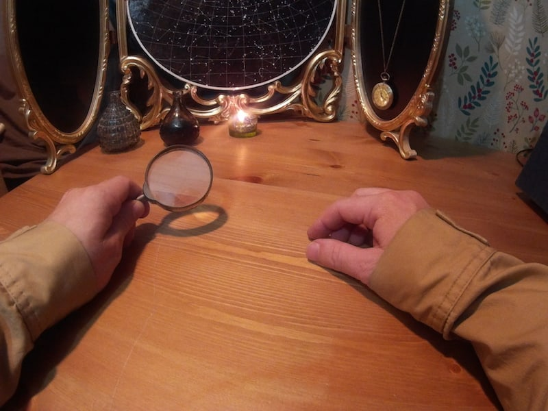 Hands of a detective holding magnifying glass on a table set with mysterious objects.