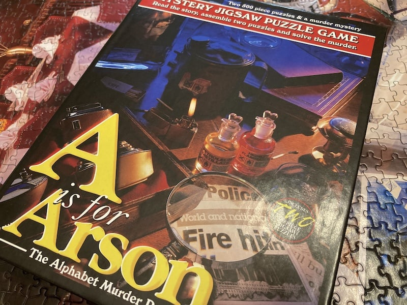A is for Arson box art, shows an ominous scene with various chemicals and a zippo lighter.