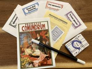 4 sealed envelopes a Poster for Professor Conundrum's show, a magic want, and a deck of cards.