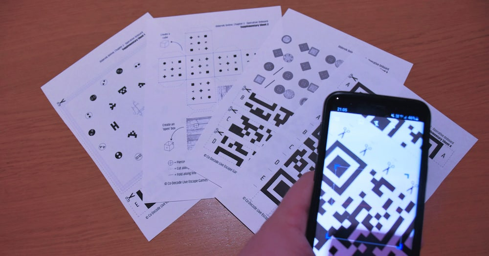 A phone scanning a QR code fom a collection of printed puzzle pages.
