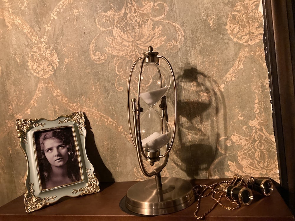 In-game: A photo of an actress, an hourglass, and opera glasses on a shelf.
