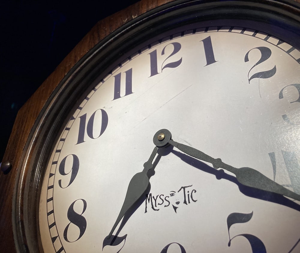In-game: Closeup of a lage clock with the Myss Tic logo on its face.