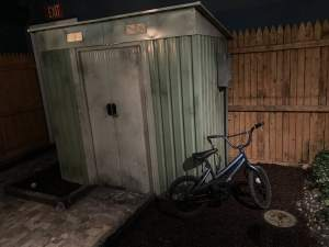 In-game: A storage shed and a bike in a yard.