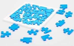 29 translucent blue acrylic jigsaw pieces and a white frame that fits them.