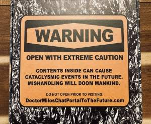 "A foil-covered box with an orange warning that reads: ""Open with extreme caution. Contents insid can cause cataclysmic events in the future. Mishandlign will doom mankind."""