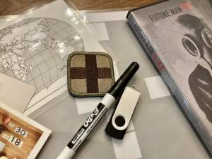 """Assorted components including, a dry erase marker, a thumb drive, a world map, and a DVD labeled """"Future Man"""""""