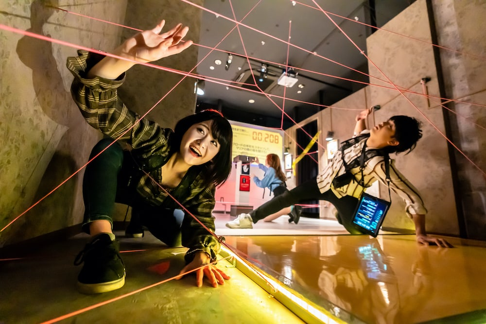 Players navigating a laser maze made of string.