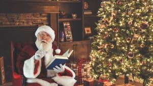 Santa sitting beside a Christmas tree reading.