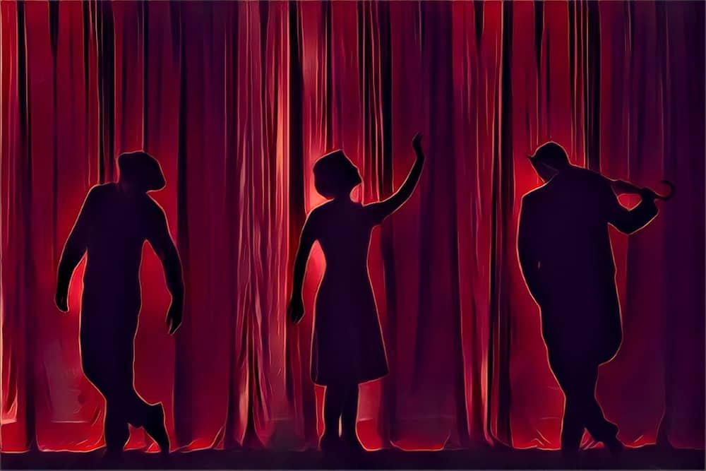 Silhouettes of three performers on stage seen through a red curtain.