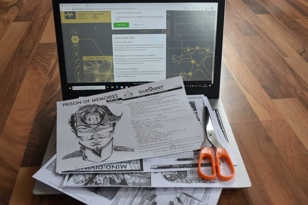 An assortment of printed components, a scissor, and a laptop.
