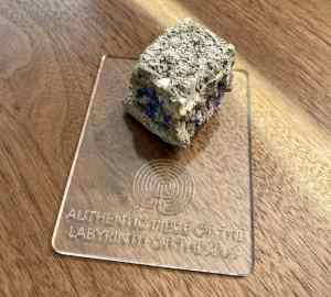 """A chunk of stone with symbols painted on it. The base reads, """"Authentic piece of the Labyrinth of Theseus."""""""