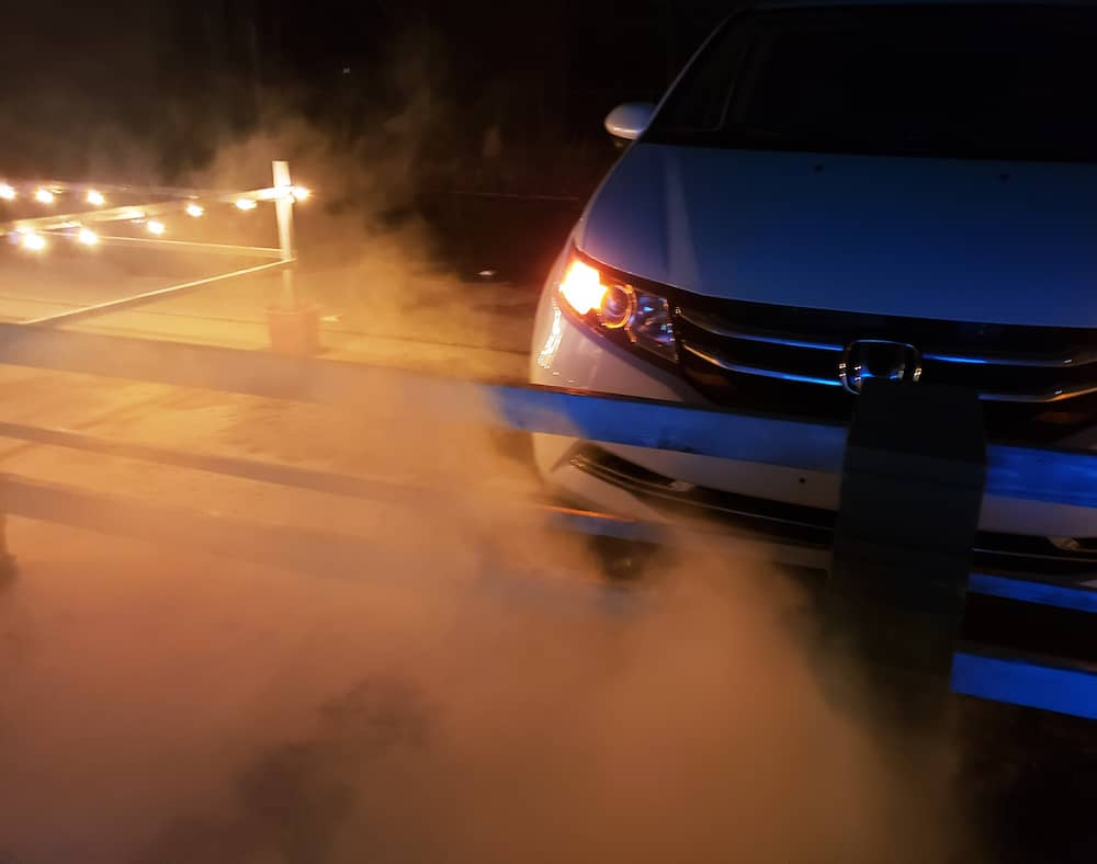 A parked car surrounded by lights and artificial fog.