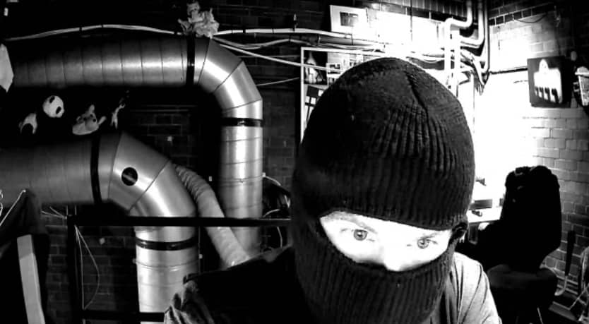 View of a masked person through a webcam.