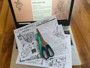 Printed game materials, scissors, and a pen sitting on a laptop.