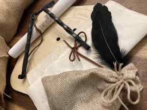 An assortment of relic items including a burlap bag, and a raven's feather.
