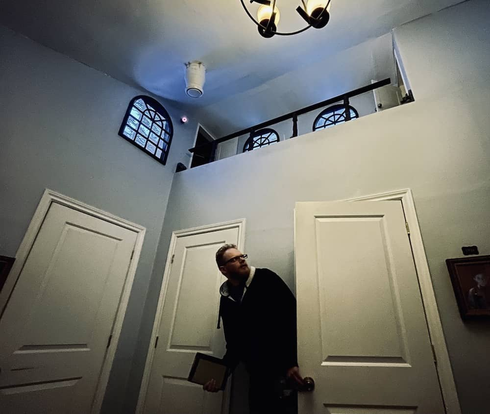 A person entering into a strangely shaped room with high ceilings.
