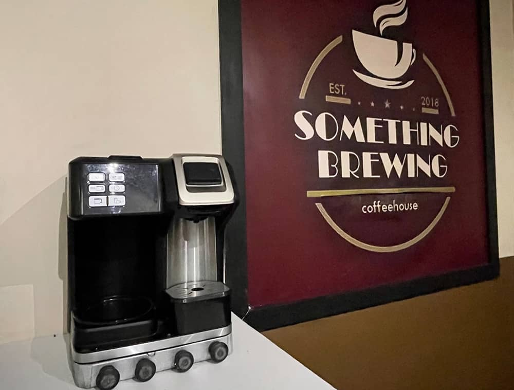 A coffee machine beside a post for the Something Brewing Coffee house.