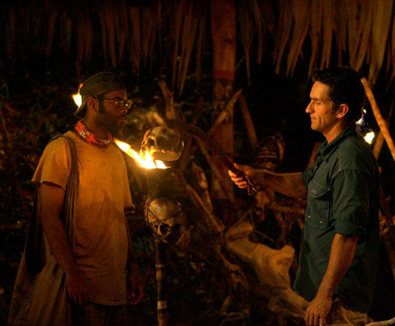 two men standing in front of a torch about to be snuffed from the reality tv show survivor