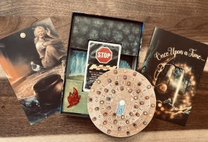 """Assorted box elements include a deck of cards, an image that looks like it's from a fairy tale, a decoder wheel, a glowing red maple leaf, and a card with the box art labeled, """"Once upon a time..."""""""