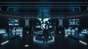 An agent wearing black briefing us from a futuristic war room.