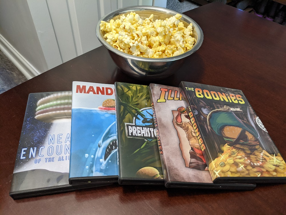 "An assortment of parody DVD boxes beside a bowl of popcorn including, ""The Boonies"" ""Indiana Bones,"" and ""Mandibles."""
