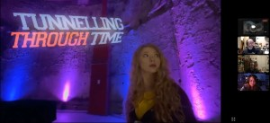 Tunnelling Through Time title card over Zoom. Performer looking nervously behind her while in a large cavernous space.