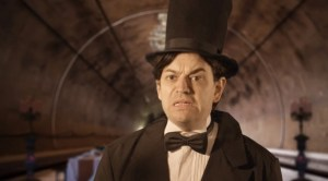 A man in a top hat and dated suit with a ghastly expression on his face.