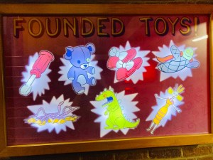"""Illuminated scoreboard of """"Founded Toys"""" all 7 are lit."""