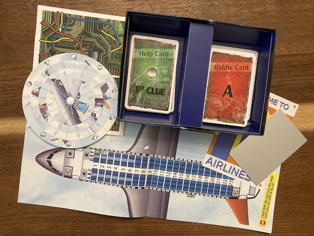 Assorted game components includes a seating chart for an airliner, riddle and help cards, a solution wheel, and a mirror.
