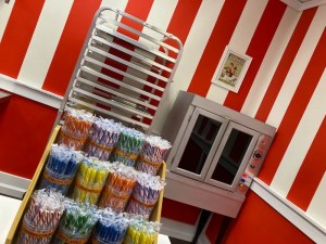 Assortment of candy canes on display in a candy shop. An oven in the background.